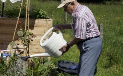 Claude geeft water op de Zintuigentuin