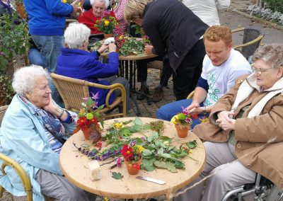 op het terras van Haarlemse Volkstuindervereniging herfstbloemstukjes maken